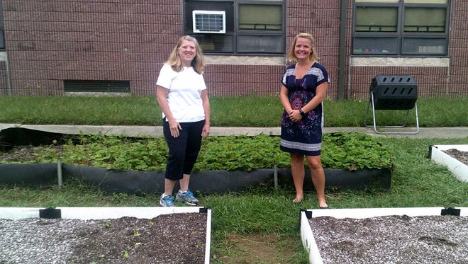 Anne Fisch (left), chair of Mary F. Janvier Elementary School's Green Team, and Celeste Serrano, grant author, are pictured in the school's garden.