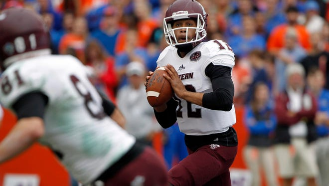 Nov 22, 2014; Gainesville, FL, USA; Eastern Kentucky Colonels quarterback Jared McClain (12) runs the ball out of the pocket against the Florida Gators during the second quarter at Ben Hill Griffin Stadium. Mandatory Credit: Kim Klement-USA TODAY Sports