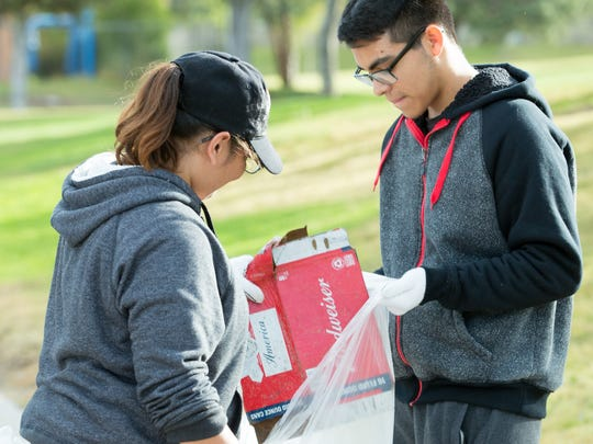 Juan Santos, 17, right, and Emerald Ramirez, 15, both students of Rio Grande Preparatory Institute, work together to pick up trash on Saturday, October 14, 2017, along the Triviz Trail during  the 23rd annual Toss No Mas campaign. The event was hosted by The City of Las Cruces Parks & Recreation Department's Keep Las Cruces Beautiful, along with New Mexico Clean and Beautiful.