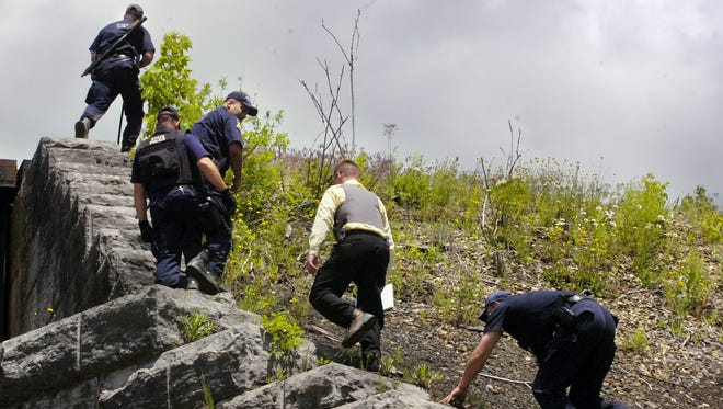 """Investigators search an area by the railroad tracks off of Rt. 79 in the Town of Colesville on June 13, 2006. Officials were looking for escaped convict Ralph """"Bucky"""" Phillips."""