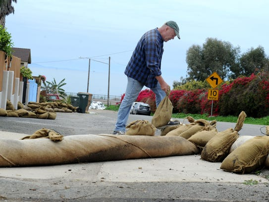 Dennis Hall places sandbags around his house Tuesday