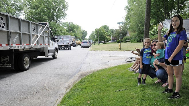 Findlay Deter, 5, watches with his mother, Katie, the parade of trucks from the City of Ashland for his 5th birthday parade on the corner of Edgewood Drive and Edgewood Court on Friday. City of Ashland recycling driver Molly Stephens arranged the parade to help Findlay celebrate his birthday. The parade included a fire truck for the Ashland Fire Department and trucks for the city street department and sanitation department.