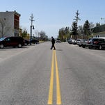 A man crosses the street in downtown Timnath on Wednesday.