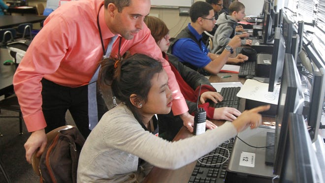 Anthony Smith, P-TECH project administrator, goes over a coding exercise with ninth-grader Esther Law, 15, in an intro to information technology class that is part of the P-TECH program at the Edison Technology Campus.