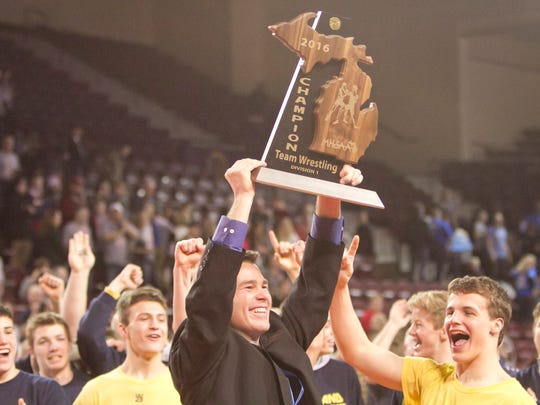 Hartland wrestling coach Todd Cheney hoists the state Division 1 championship trophy in 2016.