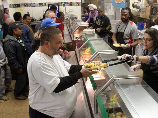 Volunteers and the Plainfield's Sodexo food service staff serve Thanksgiving fare including turkey and gravy and collard greens to people from the community at Hubbard Middle School's first Thanksgiving meal for the needy.