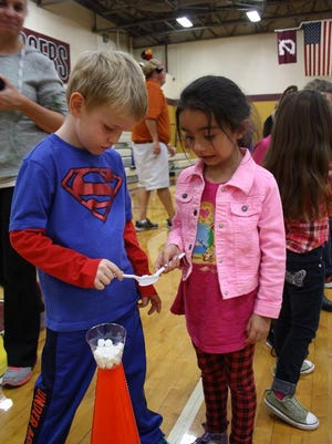Miles Conner, 5, passes a miniature marshmallow to Zephyr Sohi, 5, during the annual Clarksville Parks Department Gobbler Games at Clarksville Middle School on Saturday.