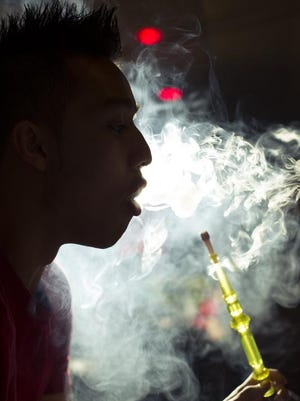 Hookahs are water pipes smoked with flavored tobacco that are popular in the Arab world. <137>Critics say they cause health problems and tobacco addictions among youths. Alex Nguyen blows smoke at Mist Hookah Lounge in Troy, which also cracked down on the cafés. <137>