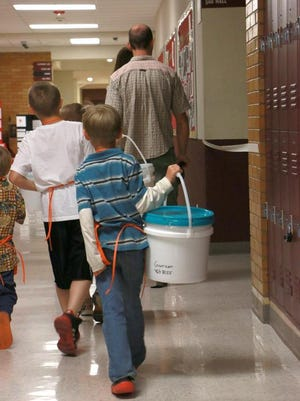 Kids walk down the hallway with 72 hour kits they made at the annual Emergency Preparedness Expo on Saturday May 3, 2014 at Cedar High School.