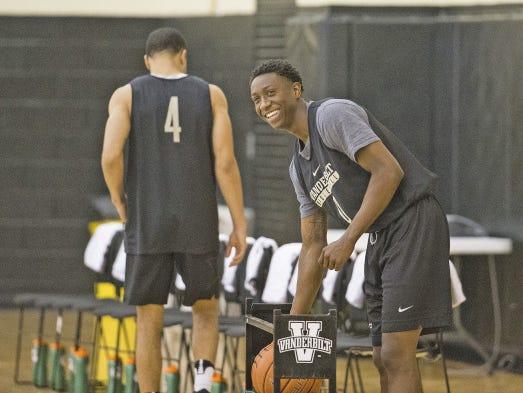 Vanderbilt freshman Saben Lee smiles and grabs a basketball at summer practice alongside Xavier transfer Larry Austin (4).