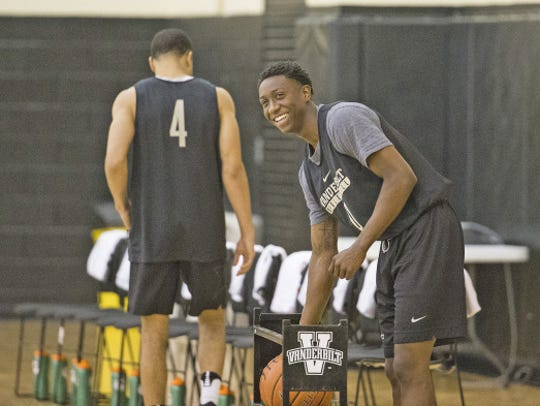Vanderbilt freshman Saben Lee smiles and grabs a basketball