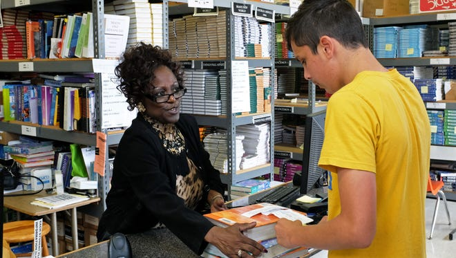 Damian Sampaga, 14, receives his textbooks for the coming year from Salinas High's Patricia McWhorter.