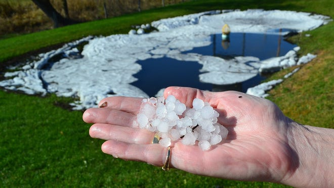 Karen Thompson holds a handful of hail taken from one of two retention ponds outside of her convenience store, Stiles Junction Food & Fuel, located on Highway 22 just west of of Highway 41.
