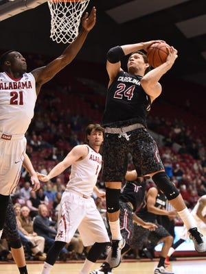 Feb 24, 2015; Tuscaloosa, AL, USA; South Carolina Gamecocks forward Michael Carrera (24) grabs a rebound in front of Alabama Crimson Tide guard Rodney Cooper (21) during the second half at Coleman Coliseum. Alabama won 59-51.