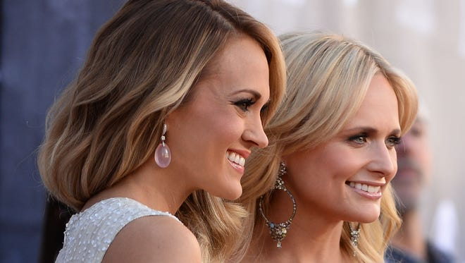 Carrie Underwood, left, and Miranda Lambert arrive at the 49th annual Academy of Country Music Awards at the MGM Grand Garden Arena on Sunday, April 6, 2014, in Las Vegas.