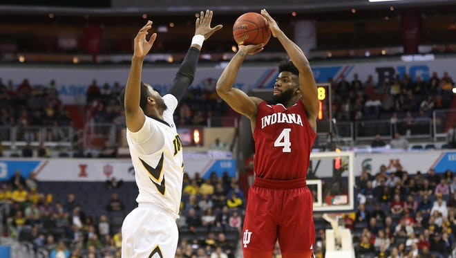 Hoosiers guard Robert Johnson (4) shoots the ball as Iowa Hawkeyes guard Isaiah Moss (4) defends in the first half during the Big Ten Conference Tournament at Verizon Center.
