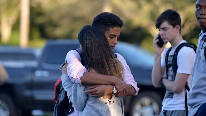 Jorge Zapata,16, a student at Marjory Stoneman Douglas High School in Parkland, Fla., embraces his mother, Lavinia Zapata, after a mass shooting on Feb. 14, 2018, at the school.