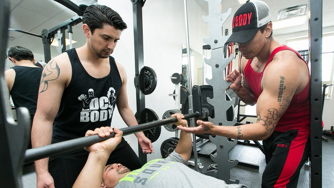 Gabe Montoya lifts weights while he is spotted by Davi Alarcon, left, and trained by DC Body owner David Chacon on Monday, March 7, 2016 at the private fitness studio located at 951 N. Solano Drive, Ste. C.