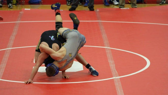 A Maysville wrestler (black singlet) has a suicide ribbon on his singlet to remember Gable Connors, who committed suicide in 2013. Gable was the son of Maysville High School head wrestling coach Shawn Connors, and the Pin Suicide tournament is held in his honor to bring awareness of youth suicide and its prevention.