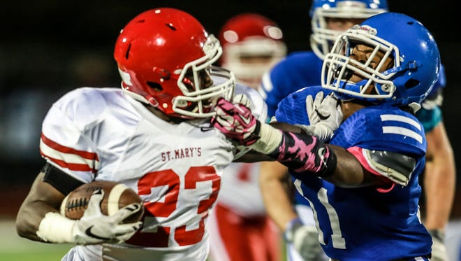 Orchard Lake St. Mary's Troy Marks catches the ball, before being tackeld by Novi Detroit Catholic Central's Chyle Johnson during the first half at Catholic Central  in Novi on Oct. 9, 2015.