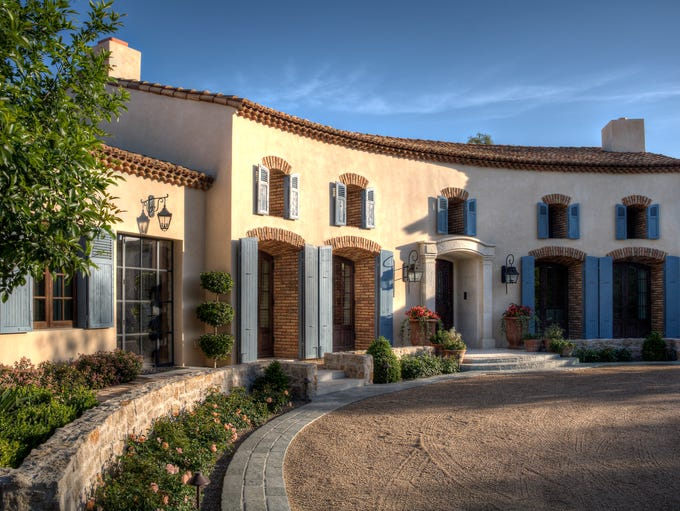 The home's red tile roof, off-white stucco walls and