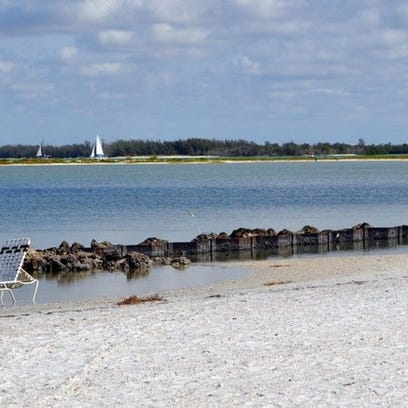 Looking from Hideaway Beach's south beach, Sand Dollar Island with low vegetation is clearly visible with the Marco River and the Australian pines of Keewaydin Island in the background.