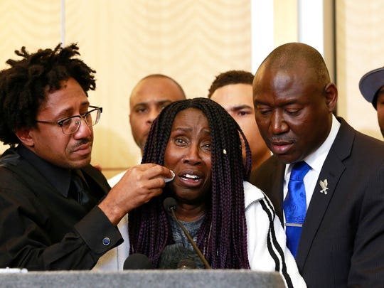 As Sequita Thompson, center, discusses the shooting of her grandson, Stephon Clark, Clark's uncle, Curtis Gordon wipes a tear from her cheek during a news conference, Monday, March 26, 2018, in Sacramento, Calif. Clark, who was unarmed, was shot and killed by Sacramento police officers a week ago who were responding to a call about a person smashing car windows. At right is attorney Ben Crump.