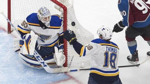 St. Louis Blues goalie Jordan Binnington, left, makes a save as Robert Thomas, right, reaches for the rebound during first period against the Colorado Avalanche in an NHL hockey playoff game Sunday in Edmonton, Alberta.