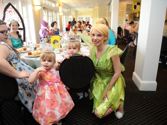 Raelynn, 3, and Carleigh, 2,  have lunch with Tinkerbell, one of many princesses,  at the 2015 Cold Stone Creamery Fairy Tale Ball benefiting Ark Crisis Child Care Center.