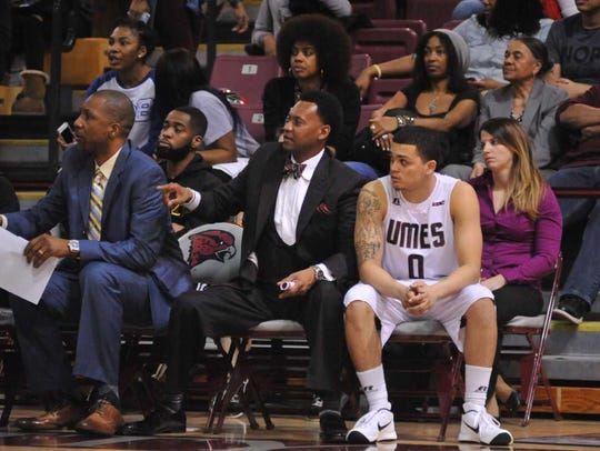 Cliff Reed coaches the UMES men's basketball team from the sidelines sitting next to guard Ryan Andino.
