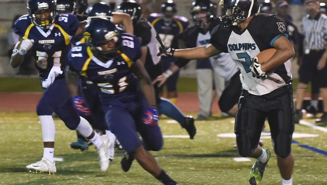In this file photo, Southern High Dolphins' Lee Burgos runs the ball against the Guam High Panthers  in an Interscholastic Football League game. Integrity Scouting Report LLC will hold the ISR Evaluation Camp from 8 a.m. to 5 p.m. Aug. 6 at John F. Kennedy High School.