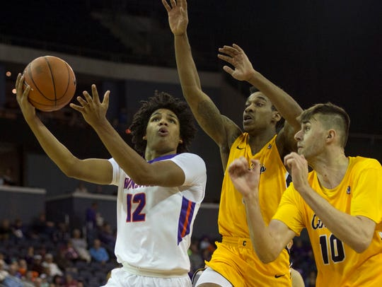 Dru Smith (12) goes up for a layup against Canisius defenders in the University of Evansville's win on Saturday.