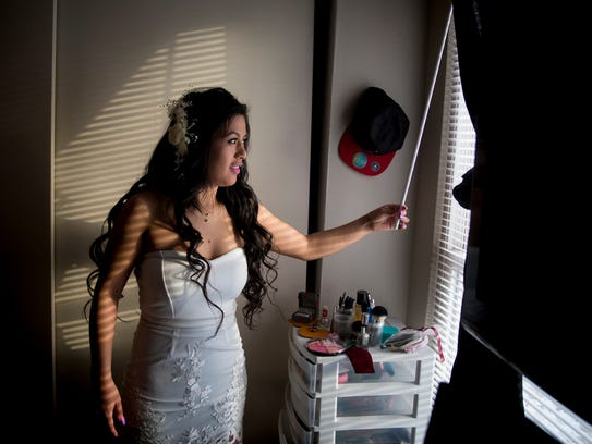 Sandra Mendoza opens the blinds in her Springdale home