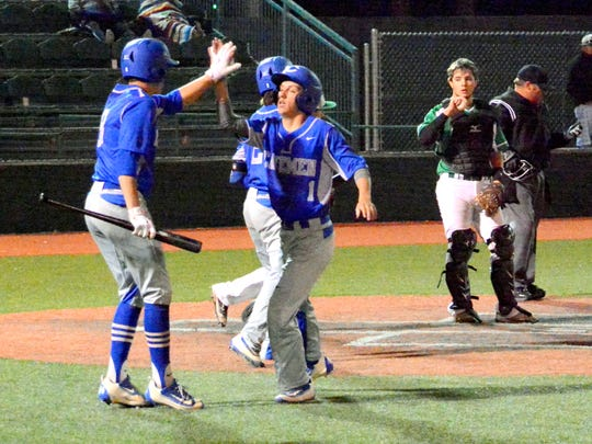 Carlsbad's Nate Arrington congratulates Jordin Molina for scoring a run in the bottom of the fourth inning Saturday.