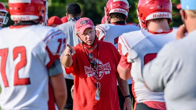 Harrisburg head football coach Steve Hopkins, center, addresses his players during preseason practice Aug. 18 at Harrisburg High School.