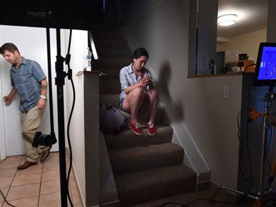 """In a Tuesday, July 21, 2015 photo, actors Jason Stange and Lisa van Dam-Bates wait outside a bedroom for their scenes during filming for the movie """"Marla Mae"""" in Olympia, Wash. Stange was arrested on July 24, 2015, by federal agent for an outstanding probation warrant after being recognized in a photo in a Washington state newspaper that ran a story about the low-budget horror movie. Stange pleaded guilty to an armed bank robbery in 2006 and was given a 117-month prison sentence. A federal probation violation warrant was issued last year after Stange left a halfway house in Spokane. (Tony Overman, The Olympian via AP)"""