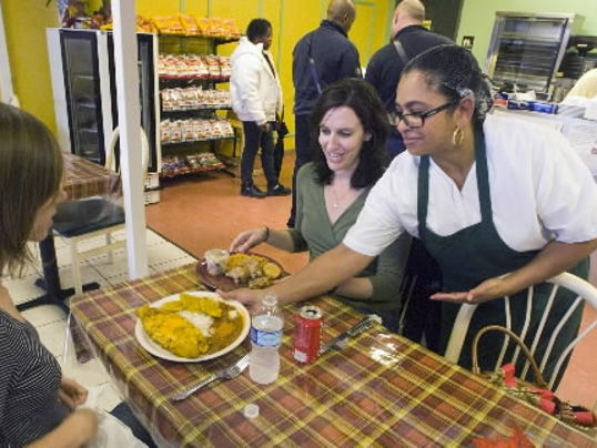 Julita Rivera Sanchez serves food to Sarah Noble and Erin Casey, who were trying Mi Caldero for the first time.