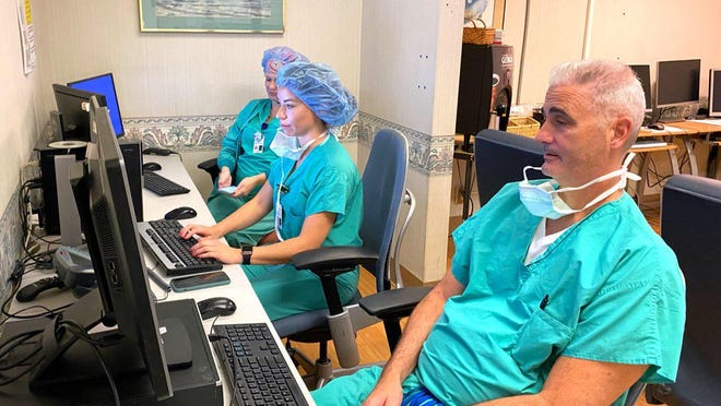 Neurosurgeon Jean Marc Guitton and physician assistant Chelsea Manning review cases in a surgical area of University Hospital.