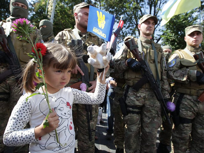 A girl stands in front of members of the Sich special volunteer battalion during a ceremony on Aug. 26 in Kiev, Ukraine.