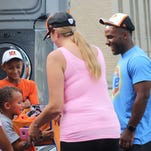 Cincinnati Bengals running back (left) Giovani Bernard signs 9-year-old Nate's Bengals t-shirt after presenting his family with a year supply of clothing.