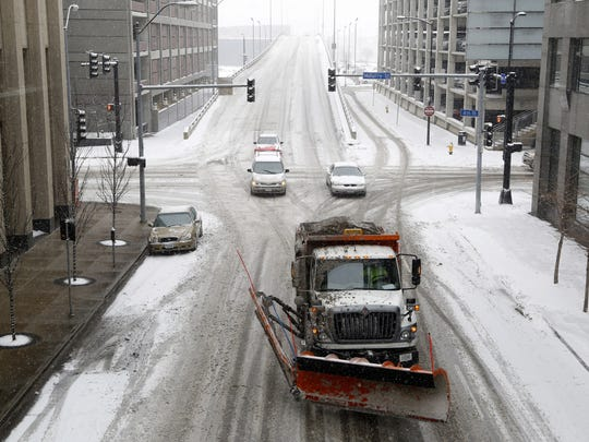 A snowplow clears a path along Eight Street in Des Moines. The city's policy is to concentrate its efforts on designated snow routes during storms, then clear residential streets when the snow is over.