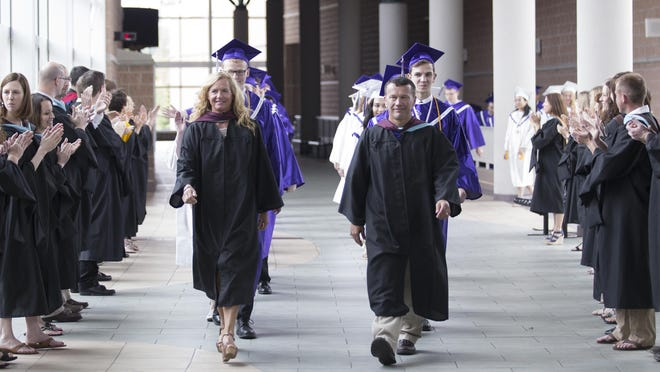 Students are led to the ceremony through Lakeview High School's faculty Sunday.