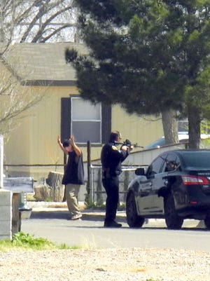 A suspect exits a home during a police stand off Wednesday in the 400 block of Cleveland Avenue in Artesia.