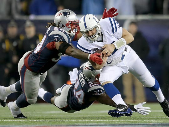Andrew Luck (12) scrambles for 5 yards and then is tackled by New England Patriots outside linebacker Dont'a Hightower (54) and Darrelle Revis (24) in the first quarter.