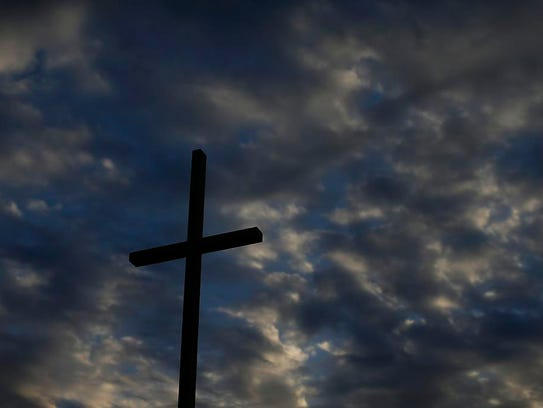 A cross against a colorful sky at Our Lady of Lourdes