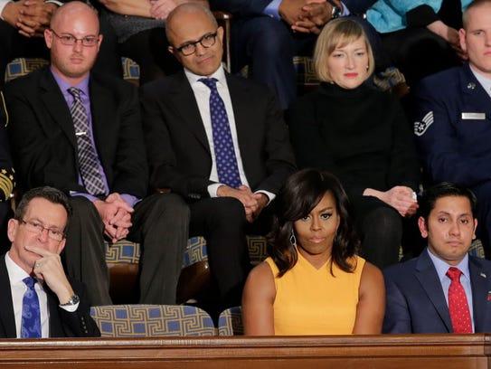 Satya Nadella, behind former First Lady Michelle Obama,