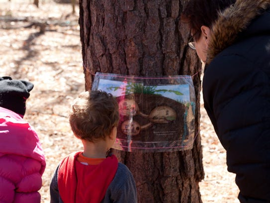 Children reading story book pages attached to trees