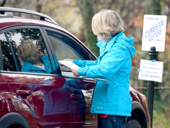 Wendy Solms helps a voter at the curbside voting parking