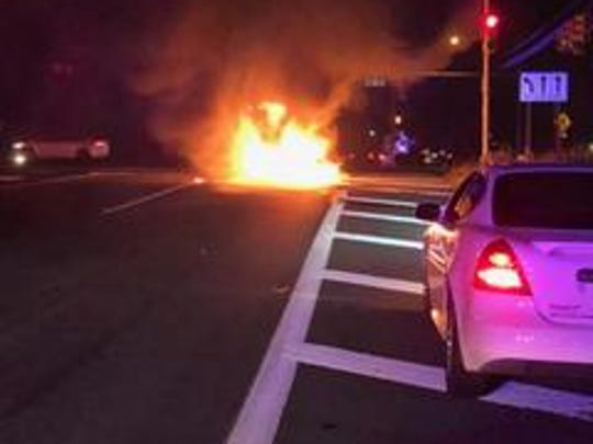 A Monroe woman was rescued from her burning car by