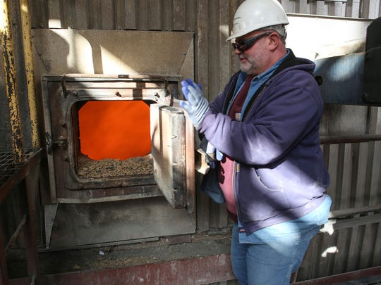Bernie Caulfield, an employee at PacifiCorp's Jim Bridger coal plant in southwestern Wyoming, opens an observation door to show burning coal on Dec. 7, 2016.